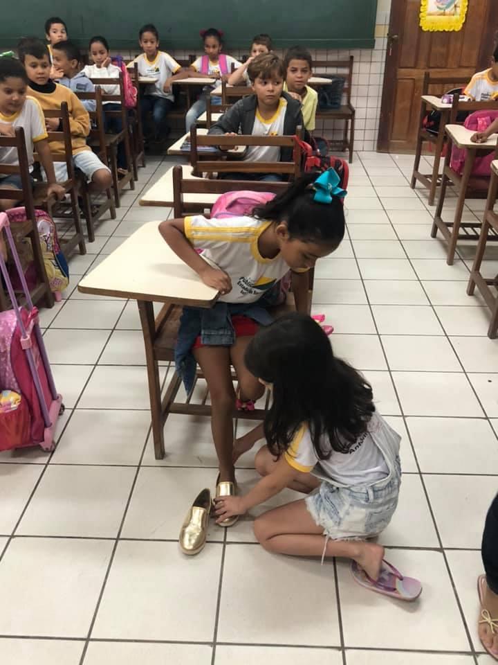 Aluna doa sapato e se ajoelha para calçar pés da coleguinha - Papo de Pai