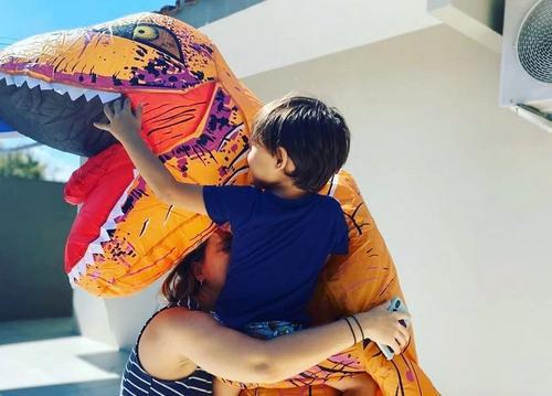 No litoral de São Paulo, um médico se veste de dinossauro para poder abraçar filho